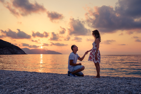 Romantisch huwelijksaanzoek op het strand bij de kust bij zonsondergang over het overzees. Jong paar in liefde