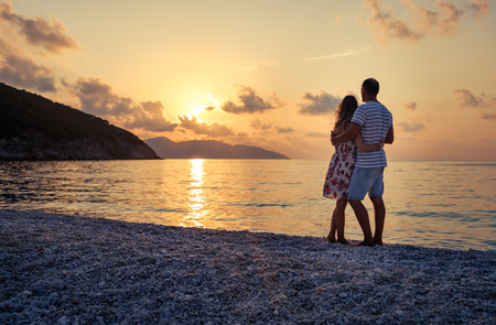Young couple in love standing on the beach at the seaside enjoying romantic evening and watching sunset. Family have a rest on the beach in summer. Stock Photo