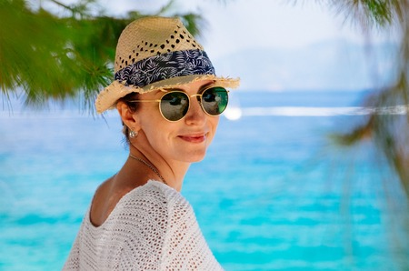 Beauty tanned and stylish young woman in white clothes, straw hat and sunglasses standing at the seaside in sunny summer day. Travel and vacation concept.
