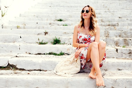 summer dress: Beauty tanned and stylish young woman in dress sitting on steps in sunny bright summer day. Travel and vacation concept.