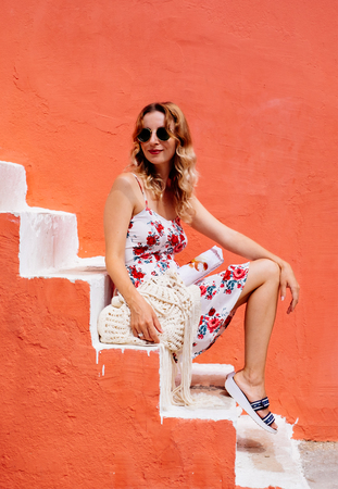 Beauty tanned and stylish young woman in dress sitting on steps in sunny bright summer day. Travel and vacation concept.