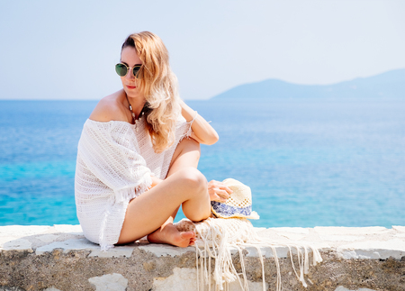 european: Beauty tanned and stylish young woman in white clothes, straw hat and sunglasses sitting at the seaside in sunny summer day. Travel and vacation concept.