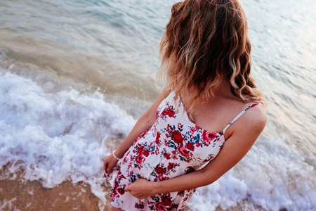 ocean waves: Beauty young woman in stylish dress standing on the beach at sunset over the horizon and looking away. Travel and vacation concept.