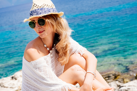 Beauty tanned and stylish young woman in white clothes, straw hat and sunglasses sitting at the seaside in sunny summer day. Travel and vacation concept.