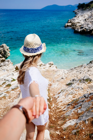 Beauty young woman in white clothes, straw hat and sunglasses holding man by hand and walking down to the beach at the seaside in sunny summer day. Travel and vacation concept. Follow me Banco de Imagens