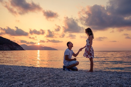 Romantic marriage proposal on the beach at the seaside at sunset over the sea. Young couple in love Banco de Imagens