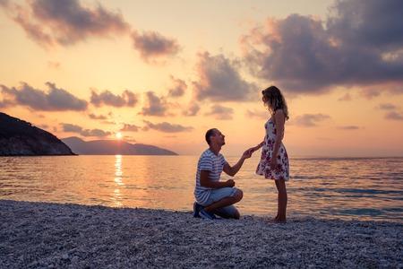 Romantisch huwelijk voorstel op het strand aan de kust bij zonsondergang over de zee. Jong stel verliefd