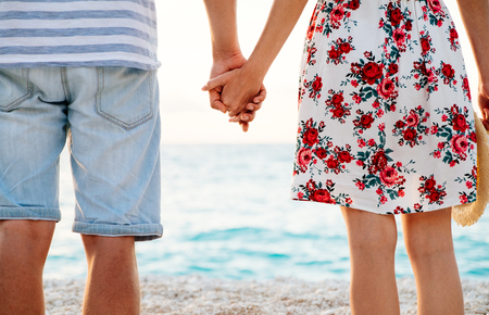 Happy young couple in love standing on the beach holding hands and watching sunset over the sea. Travel and vacation concept. Stock Photo