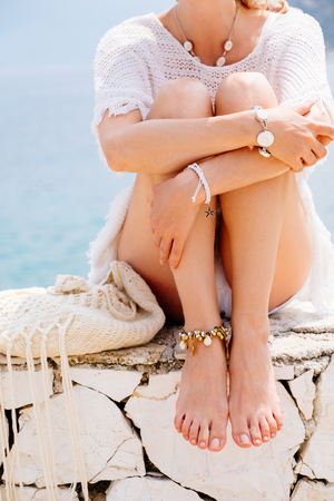 Beauty tanned and stylish young woman in white clothes sitting at the seaside in sunny summer day. Travel and vacation concept.