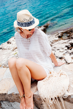 freedom: Beauty tanned and stylish young woman in white clothes, straw hat and sunglasses sitting at the seaside in sunny summer day. Travel and vacation concept.