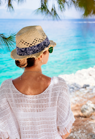 Beauty tanned and stylish young woman in white clothes, straw hat and sunglasses standing at the seaside in sunny summer day and looking away. Travel and vacation concept.