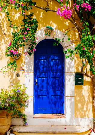 Facade of traditional Greek building with beautiful pink flowers. Greece. Kefalonia