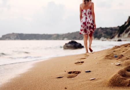 아름다움 젊은 여자가 지평선 넘어 석양 모래 발자국을 떠나 해변에서 맨발로 걷고 세련된 드레스. 여행 및 휴가 개념입니다.