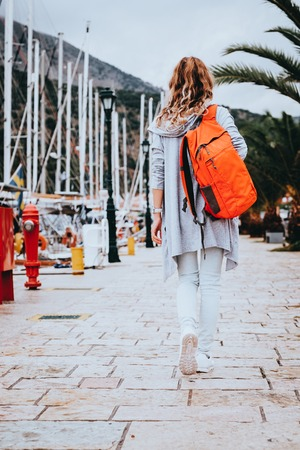 Young woman with orange backpack on her shoulder walking along pier with yachts in old european town in summer day. Travel and vacation concept.