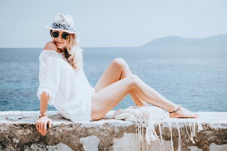 Schönheit gebräunt und stilvolle junge Frau in weißen Kleidern, Strohhut und Sonnenbrille am Meer in sonnigen Sommertag sitzt. Reisen und Urlaub Konzept.