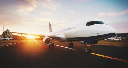 석양 공항 활주로에 서 서 화이트 상업용 비행기. 여객 비행기가 이륙하고 있습니다. 비행기 개념 3D 그림입니다.