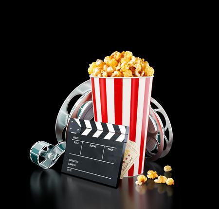 Popcorn, cinema reel, disposable cup, clapper board and tickets at black background. Concept cinema theater 3D illustration. Foto de archivo