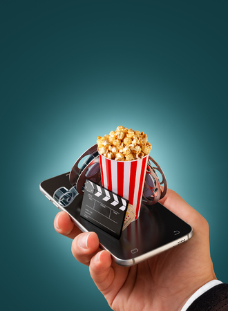smarthone: Smartphone application for online buying and booking cinema tickets. Live watching movies and video. Unusual 3D illustration of popcorn, cinema reel, clapper board and tickets on smarthone in hand