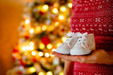 La mujer embarazada sostiene los pequeños zapatos lindos de los bebés en las manos en el árbol de navidad. Foto de archivo