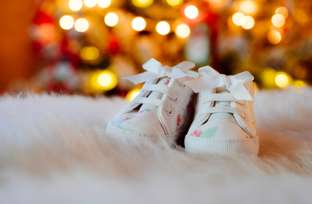 Cute little infants shoes at Christmas tree.
