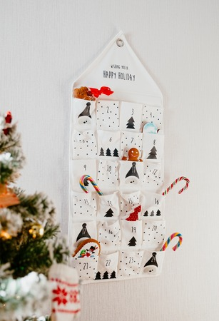 christmas holyday calendar with gifts and sweets hangs on a wall in a bright room at christmas tree
