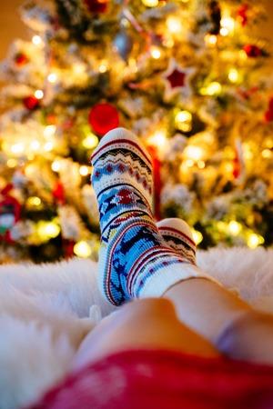 Womans Feet in woollen socks at Christmas tree. Stock Photo