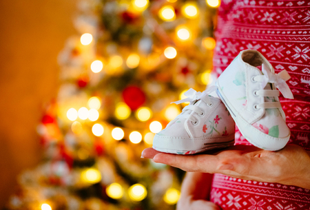 Pregnant woman holds Cute little infants shoes in hands at Christmas tree. Stock Photo