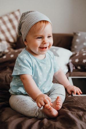 Mignon petite fille heureuse bébé jouant assis sur un lit dans une chambre . sourire de la famille ayant des blagues Banque d'images - 96347662