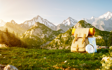 Touristic backpack with map and compass on grass field at mountain in summer day. Unusual 3d illustration of mountain landscape with fog. Travel and vacation concept