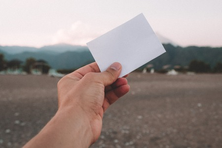 Empty paper note in hand on amazing landscape background. Travel and Vacation concept. White piece of paper with no text Stock Photo