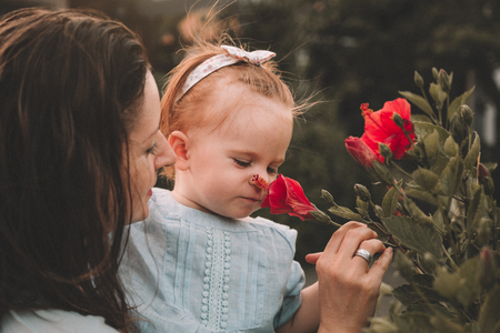 Cute little baby girl with her mother sniffing flowers in a garden in summer day.