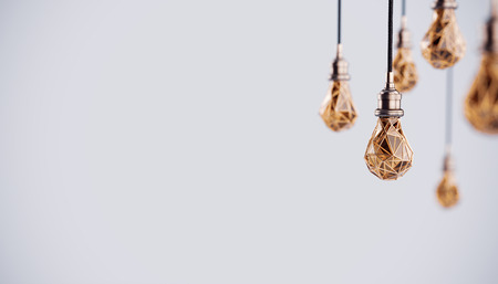 Unusual 3d illustration of hanging stylized low poly light bulbs with golden wire. Conceptual background Imagens