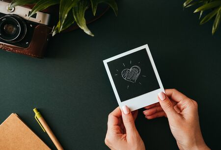 Top view of flat lay female hands holding picture with heart next to the film camera in case notebook and pen lie on dark countertop. Concept of memories of wedding trip. Advertising space