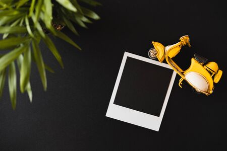 Top view of a flat lay empty  shot lying on a black table next to a green plant and a toy yellow motorcycle. The concept of pleasant summer memories. Advertising space Banco de Imagens