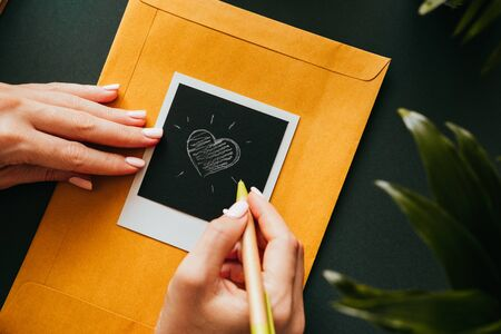 Top view of a flat lay of female hands drew a heart on a  image lying in a yellow-mail envelope. The concept of love correspondence. Advertising space