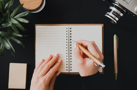 Top view of a flat lay womans hand writes a note in an open notebook lying on a black table next to the camera with a pen and writing paper. The concept of home accounting. Advertising space