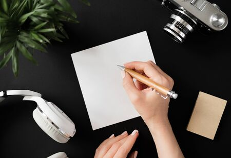 Top view of a flat lay female hand writes a note with a pen on a white sheet of paper lying next to the film camera with headphones and recording paper on a black table. Advertising space