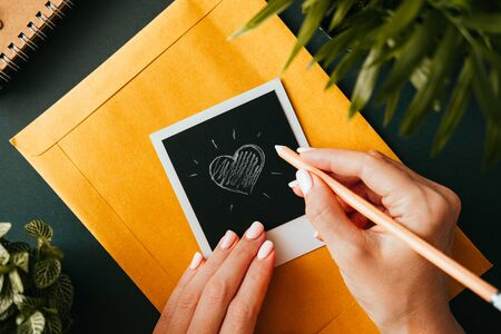 Top view of a flat lay female hand drew a heart on a  picture lying on a yellow postal envelope next to a notebook and a green plant. The concept of love correspondence. Advertising space 写真素材