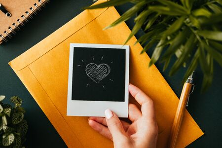 Top view of a flat lay female hand holding a  picture with a heart next to a yellow postal envelope next to a notebook and a green plant. Love letter concept. Advertising space