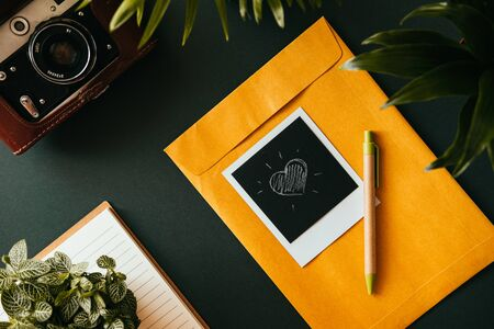 Top view of a flat lay  shot with a heart lying on a yellow postal envelope next to a film camera in a case a notebook and a pen. The concept of romantic letters. Advertising space
