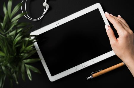 Top view of flat lay students hand holds tablet with a black screen lying on a black countertop next to a pen and headphones. Concept workspace of human with a creative profession. Advertising space