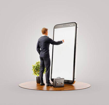 Ungewöhnliche 3D-Darstellung eines jungen Mannes, der vor einem großen Smartphone im Büro steht und den Smartphone-Bildschirm berührt. Konzept für Smartphone-Apps. Standard-Bild