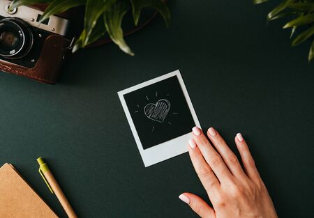 Top view of a flat lay female hand holds a photo picture with a heart next to the film camera in case and notebook and pen lie on a dark tabletop. Honeymoon memories concept. Advertising space