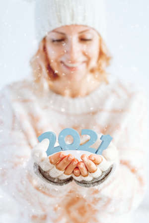 Cute woman holds 2021 in her hands. Merry Christmas and a Happy new year concept