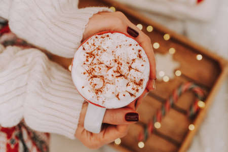 Close up of women's hands holding white mug with hot cocoa, tea or coffee and marshmallow. Winter and Christmas time concept.