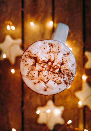 Close up of christmas white mug with hot cocoa, tea or coffee and marshmallow. Winter and Christmas time concept.