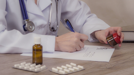 The doctor looks at medicine and writes a prescription. Stock Photo