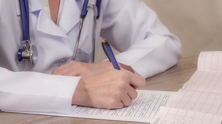 The doctor looks cardiogram and makes notes in a document. Stock Photo - 119007738