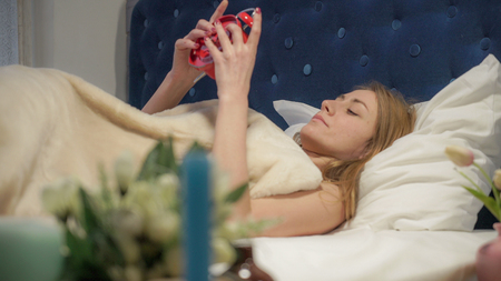 Early morning blonde turns off the red alarm and sleep on. Stock Photo - 118939050