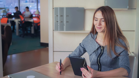 Female sitting at the personal office on shelves documents in folders. Woman speaking on touch screen tablet. She using earphones for speaking. They discussing project. Lady with long hair smile and happy to see her interlocutor. Imagens - 117144009
